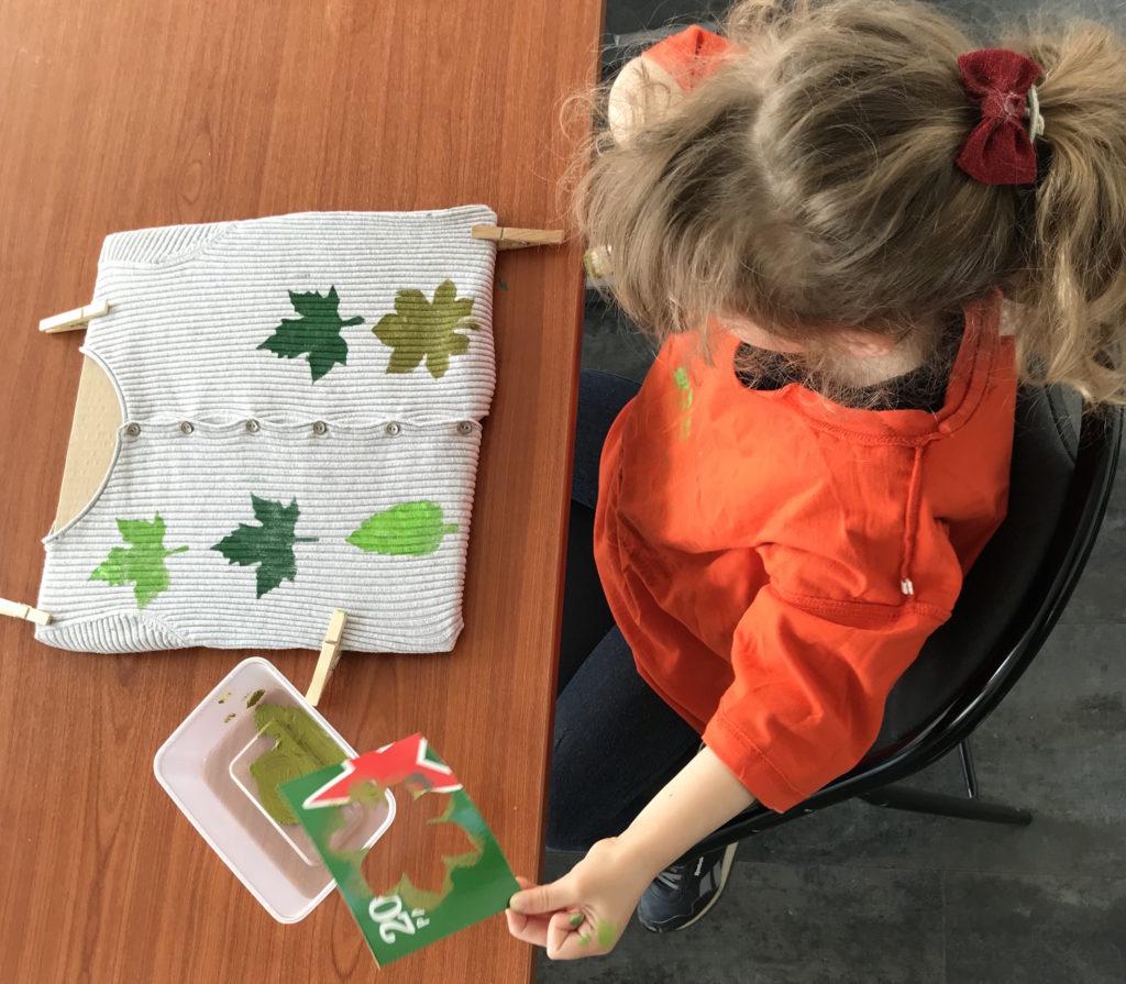 Une enfant customise son t-shirt à l'aide de pochoirs